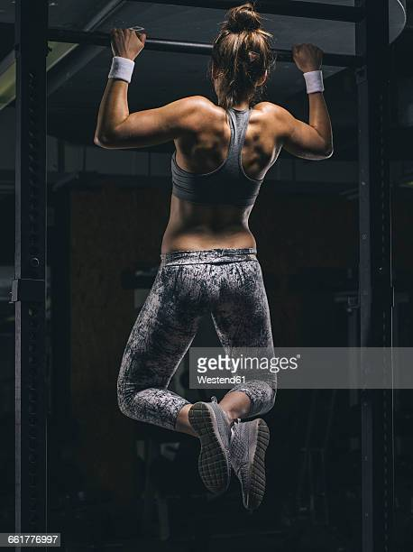 female athlete exercising chin-ups - chin ups stock photos and pictures