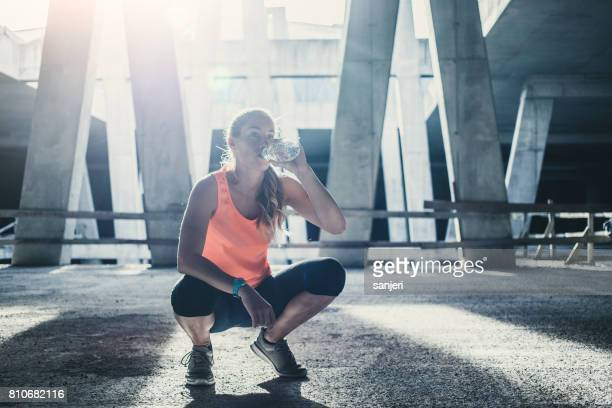 Female Athlete Exercising Outdoors, Drinking Water