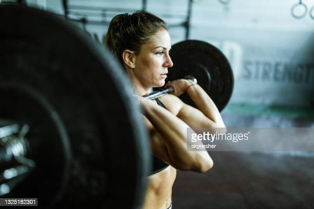 female athlete exercising strength with barbell in a health club. - women's weightlifting stock pictures, royalty-free photos & images