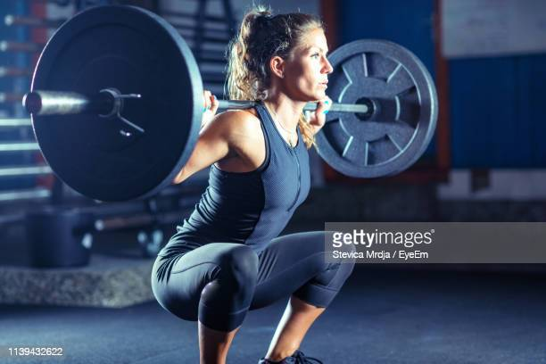 female athlete exercising with barbell in gym - barbell stock pictures, royalty-free photos & images