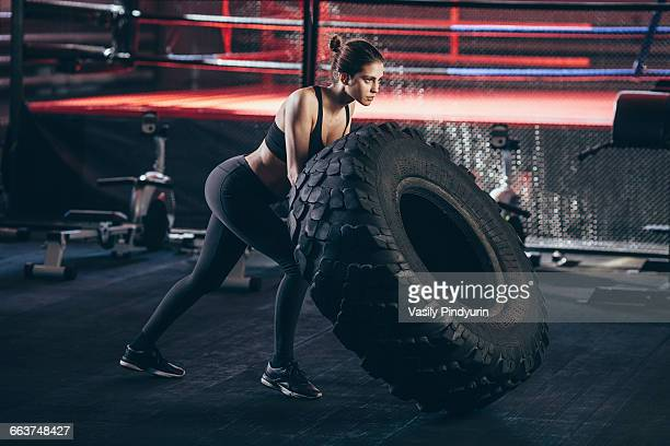 Female athlete exercising with tire at gym