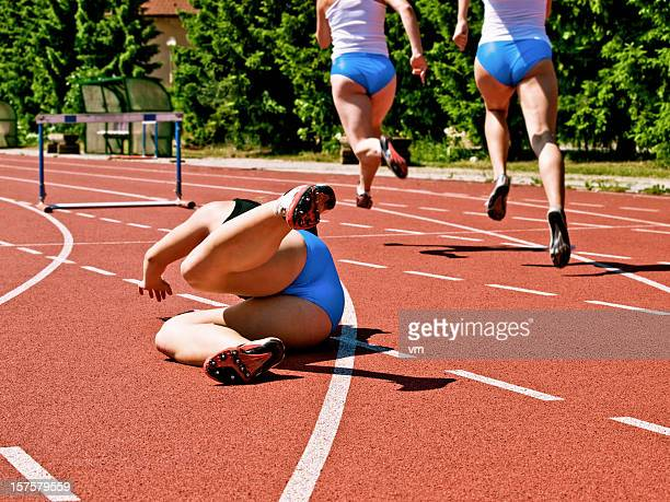 Female athlete falling down on track race