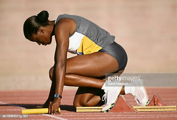Female athlete holding baton, preparing for relay race