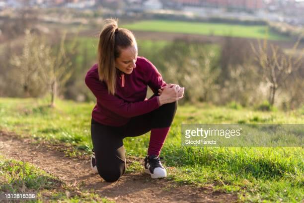 atleta femenina sosteniendo su rodilla con dolor en el parque - rodilla humana fotografías e imágenes de stock