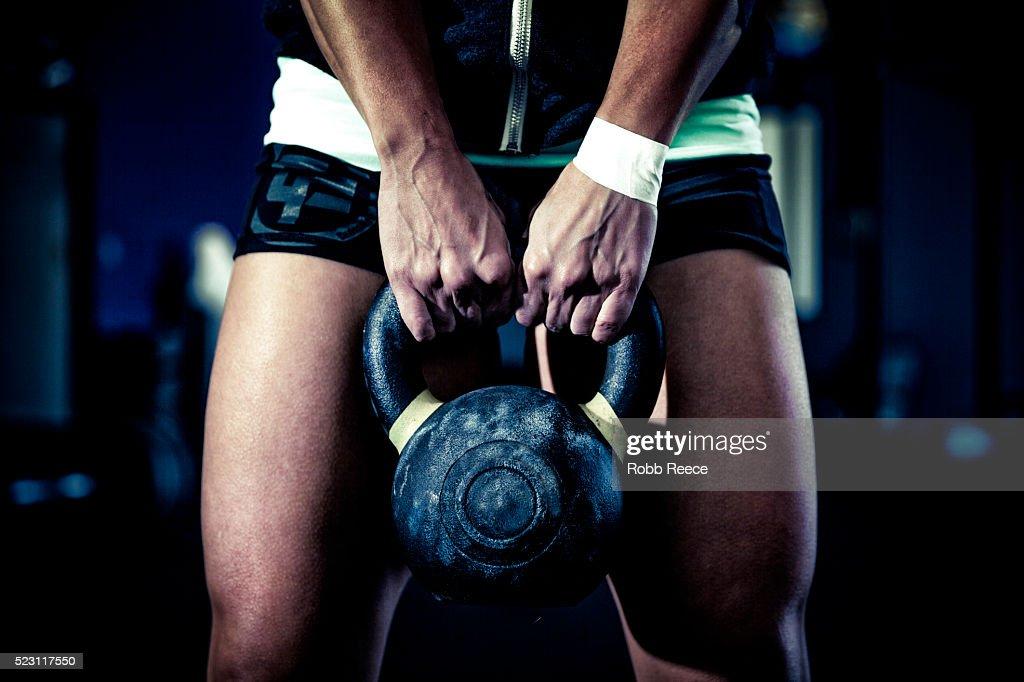 Female athlete holding kettlebell : Stock Photo