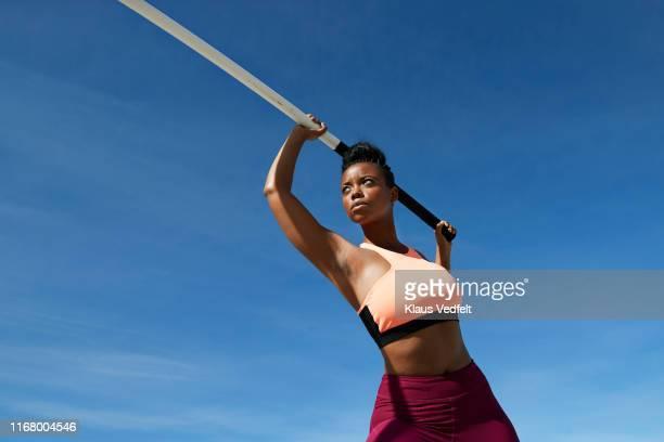 female athlete holding pole vault against blue sky - athletics photos et images de collection