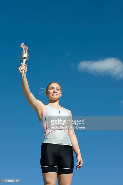 female athlete holding up torch - flame stock pictures, royalty-free photos & images