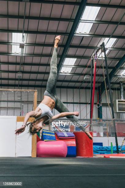 female athlete in early 30s practicing aerial cartwheel - legs apart stock pictures, royalty-free photos & images