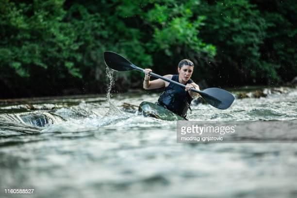 vrouwelijke atleet in kayak oefenen voor de wedstrijd dag - stroomversnelling stockfoto's en -beelden