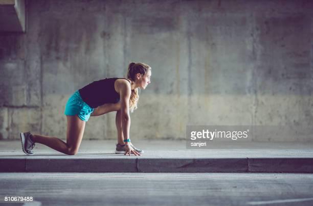 atleta femenina en posición baja en una carretera urbana - línea de salida fotografías e imágenes de stock