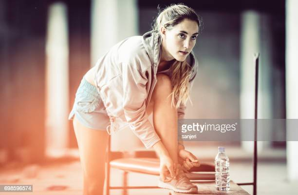 Female Athlete In Preparation For Exercising Tying Shoes