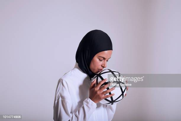 Female Athlete intensely holding football to mouth in concentration