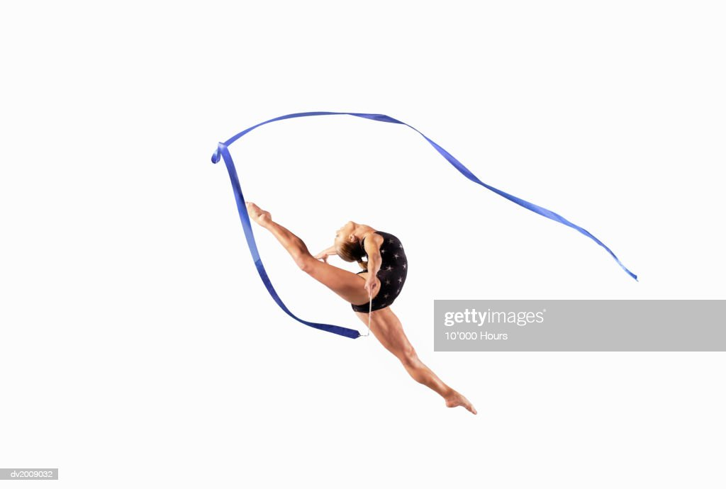 Female Athlete Jumping Gracefully Mid Air With a Ribbon : Stock Photo