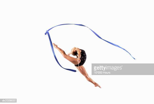 female athlete jumping gracefully mid air with a ribbon - rhythmic gymnastics stock pictures, royalty-free photos & images