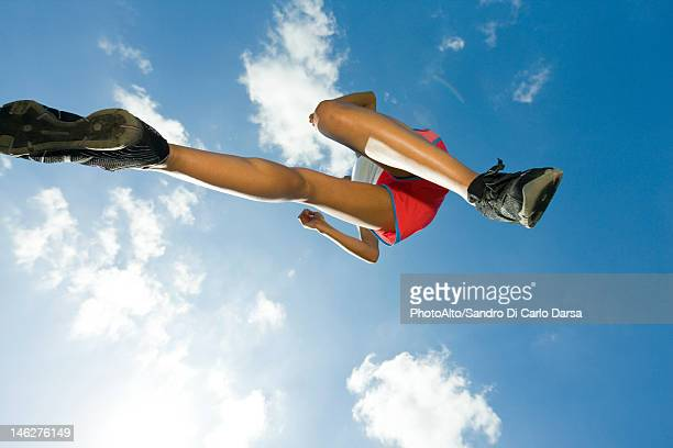 female athlete jumping in air, directly below - 靴底 ストックフォトと画像