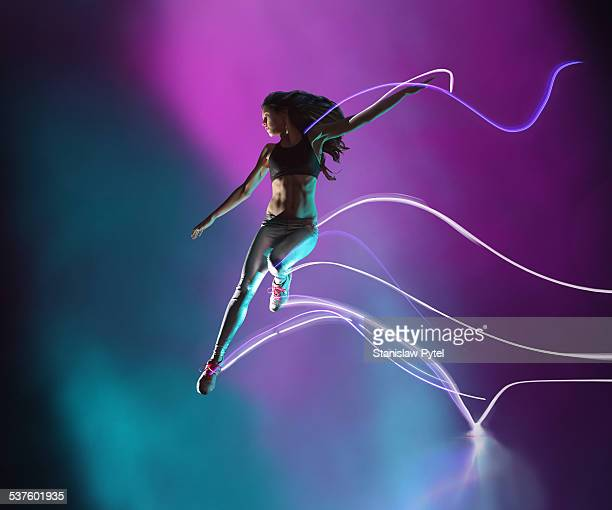 Female athlete jumping, leaving streaks of light