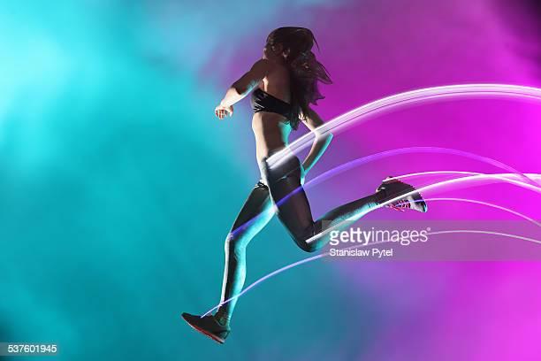 Female athlete jumping, leaving streaks of light