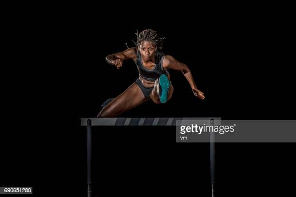 Female athlete jumping over a hurdle at night