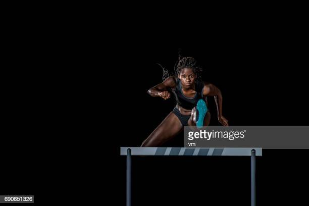 female athlete jumping over a hurdle - hurdling stock photos and pictures
