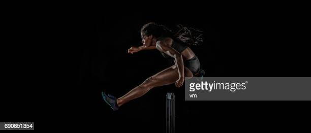 female athlete jumping over a hurdle - hurdling track event stock pictures, royalty-free photos & images