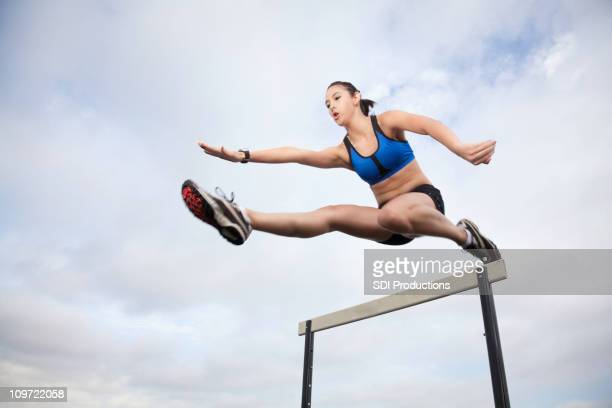 Female Athlete Jumping Over Hurdle During Track Meet