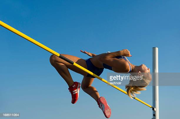 Female athlete jumping over the lath