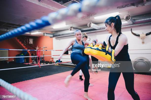 Female athlete kicking paddings held by woman in boxing ring at gym