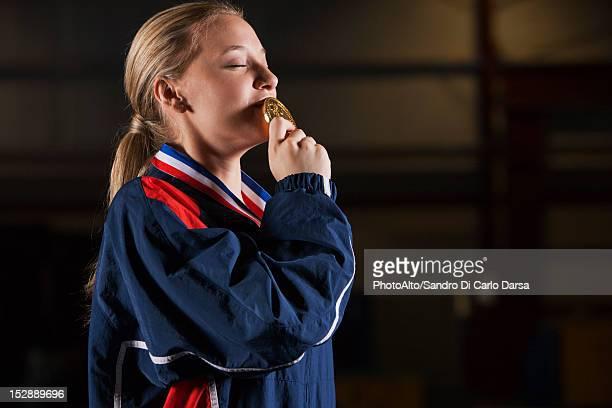 Female athlete kissing gold medal