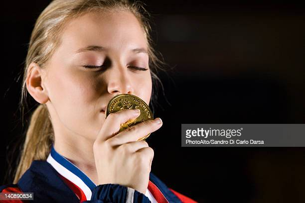 female athlete kissing gold medal, portrait - médaille d'or photos et images de collection