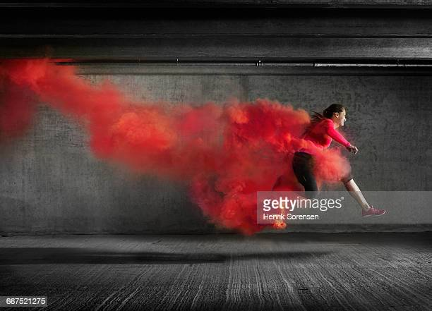 Female athlete leaping through smoke