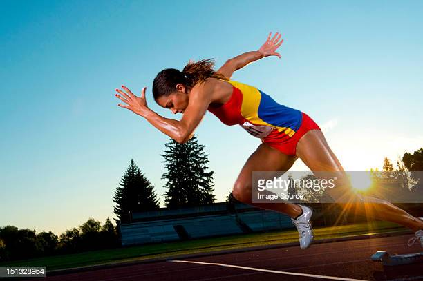 female athlete leaving starting blocks - women's track fotografías e imágenes de stock