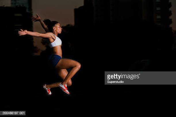 female athlete long jumping, side view, night - women's field event stock pictures, royalty-free photos & images