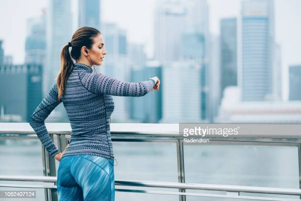 female athlete looking at her smart watch - center athlete stock pictures, royalty-free photos & images
