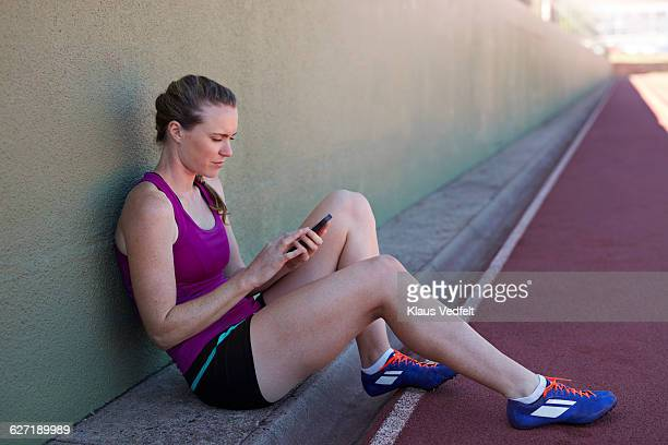 Female athlete looking at phone after practice