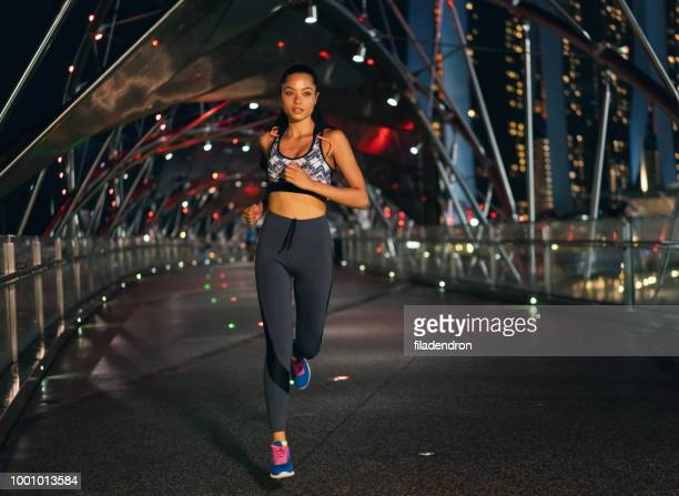 female athlete night running - asian six pack stock photos and pictures