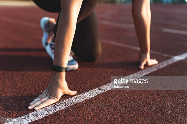 female athlete on the starting line of a stadium track - sports round stock pictures, royalty-free photos & images