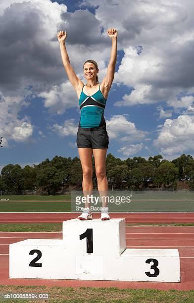 Female athlete on winner's podium on track