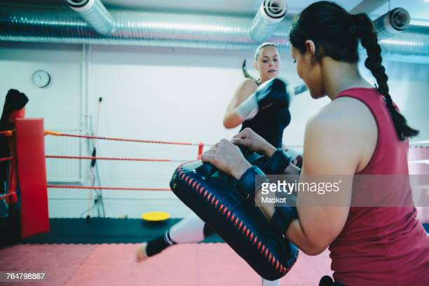 Female athlete practicing kickboxing with instructor in boxing ring at health club