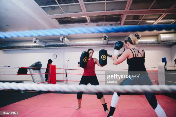 Female athlete practicing kickboxing with instructor in boxing ring at gym