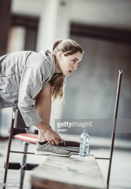 Female Athlete Preparing for Exercise, Tying Sneakers