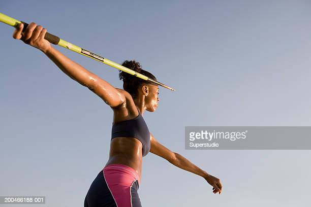 female athlete preparing to throw javelin, low angle view, side view - javelin stock pictures, royalty-free photos & images