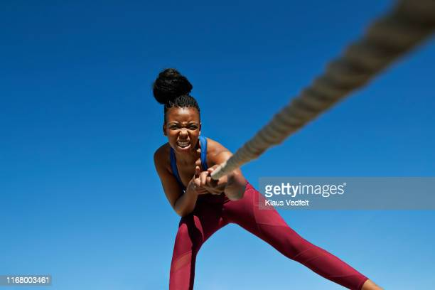 female athlete pulling rope while exercising against clear blue sky - dedizione foto e immagini stock