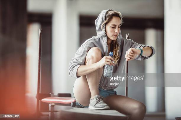 Female Athlete Resting, Drinking Water and Checking Heart Rate