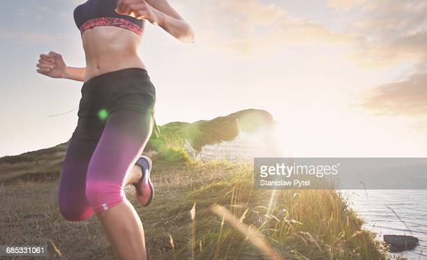 Female athlete running along cliff at sunset