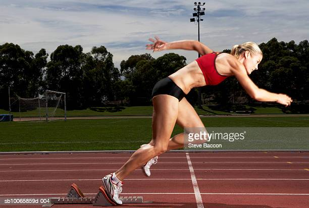 Female athlete running from starting block on track