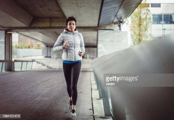 female athlete running in an urban environment - center athlete stock pictures, royalty-free photos & images