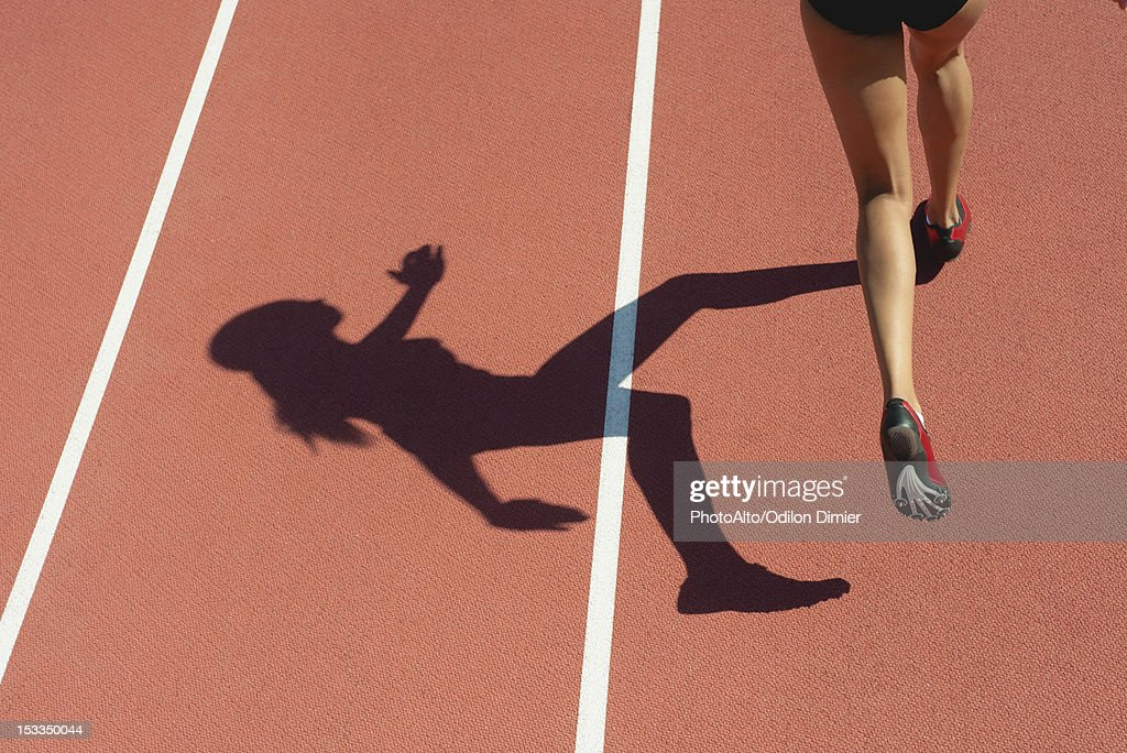 Female athlete running on track, low section, focus on shadow : Stock Photo