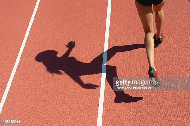 female athlete running on track, low section, focus on shadow - ombra in primo piano foto e immagini stock