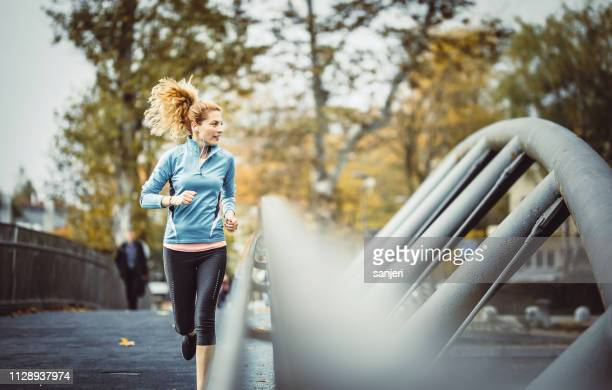 female athlete running outdoors - marathon stock pictures, royalty-free photos & images