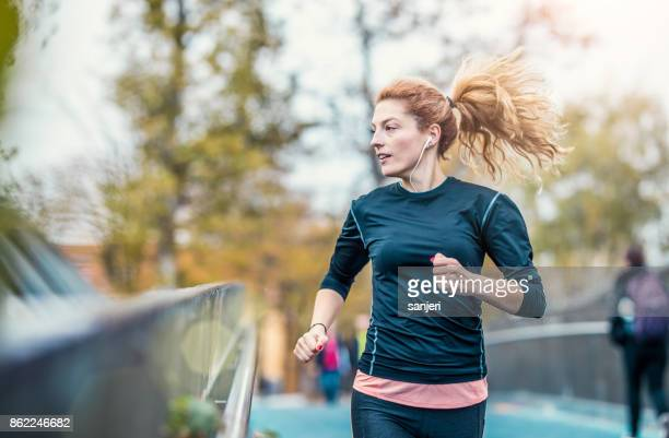 femme athlète courir en plein air - joggeuse photos et images de collection